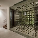 adorable large wine cellar design on glass transparent idea aside white wall and wooden brown staircase with flashing orange pallete on the wall
