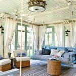 adorable modern sun porch idea with swinging set in blue tone and rattan seatng and table bneath round chandelier on wooden ceiling upn wooden floor with white curtain