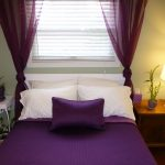 adorable purple bedroom design with sheer purple curtains to cover the small widnow with wooden side table and side lamp and white small table with greenery