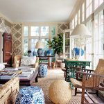 adorable sun porch idea with rattan wooden reclining chiar with round egg puff and blue oatterned side table with rattan chairs upon cream area rug with stunning wallpaper