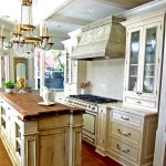 amazing chandelier design with golden accent above wooden kicthe island with inexpensive countertop before dull white cabinetry and glass storage
