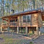 an elevated small cabin in rustic style with small front deck in the woods