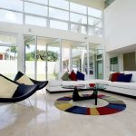 architecture interior design for white living room with sectional sofa plus colorful cushions plus glass top coffee table and black leather chairs and round rug and glass door