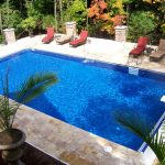 awesome rectangle pool design with red pool lounge chairs and plants plus marble floor together with metal fences