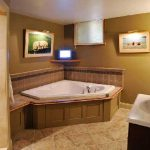 basement bathroom ideas in brown paint scheme and bathtub plus vanity units with single sink and mirror plus artistic pictures