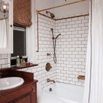 bathroom remodelling with bathtub plus curtain and vanity units plus toilet and brick tiles wall plus unique lamp
