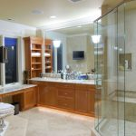 bathroom remodelling with walk in shower and wooden vanity unit with marble countertop plus sink and large mirrors and bathtub