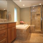 bathrooms remodeling with bath tub with tiles and bathroom vanity units with sink and mirror plus shower room with glass wall and natural tile floor