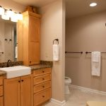 bathrooms remodeling with wooden bathroom vanity units plus sink and large mirror plus wooden chair and towel holders plus toilet