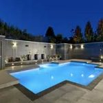 beautiful night view of stunning blue crossed shaped swimming pool with modern lighting and decorative plants surrounded with concrete fence