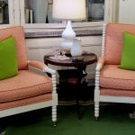 beautiful pink spool chairs with bright green pillows and round wood table a table lamp and a pair of wine glasses