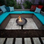 beautiful turquoise banquette design with blue gray and red cushions on concrete patio idea with round in ground fire pit