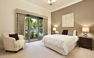 beige bedroom ideas with divan bed plus cute cushions and armchairs plus wooden nightstands plus table lamps and picture plus glass windows and door with curtains