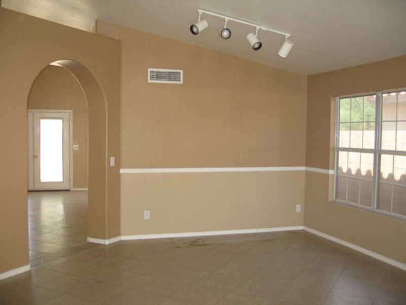 Beige Wall Painting With White Baseboard And Molding A Glass Window Without Treatment