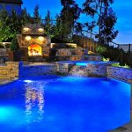 best backyard pools in curve shape combined with natural granite stone side with sauna and and living space with fireplace and armchairs