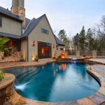 best backyard pools in curve shape with natural stone floor and small sauna plus mini fountain combined with beautiful lighting for summer