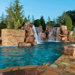best backyard pools in curve shape with natural stone floor combined with beautiful fountain and plant and flower garden