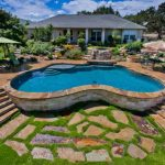 best backyard pools in curve shape with natural stone on the side combined with beautiful garden and living space with lounge pool chair and umbrella for summer time