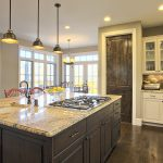 best kitchen remodeling with light cabinets with marble countertops plus island with sink and chairs and pendant lighting and wood floor plus brick wall