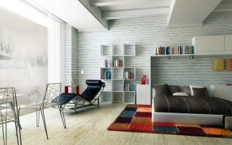 black and white brick wall for interior bedroom with large white and black panel bed and soft rug and display storage plus lounge chairs and book shelves and wooden floor