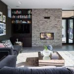 black and white brick wall in living room with black sofa and mirrored coffee table with rug underneath plus book shelves and pictures