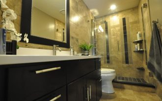 black framed wall mirror design above cream tile wall and black modern vanity design aside toilet seat and transparent walk in shower with black line accent