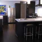 black kitchen island design with modern white black stain stools and dark bambooo flooring style beneath flashing bright modern lighting ans bronze refrigerator and blue pallete and some storage