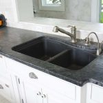 black soapstone for kitchen countertop with double sinks and double faucets plus bottom cabinetry
