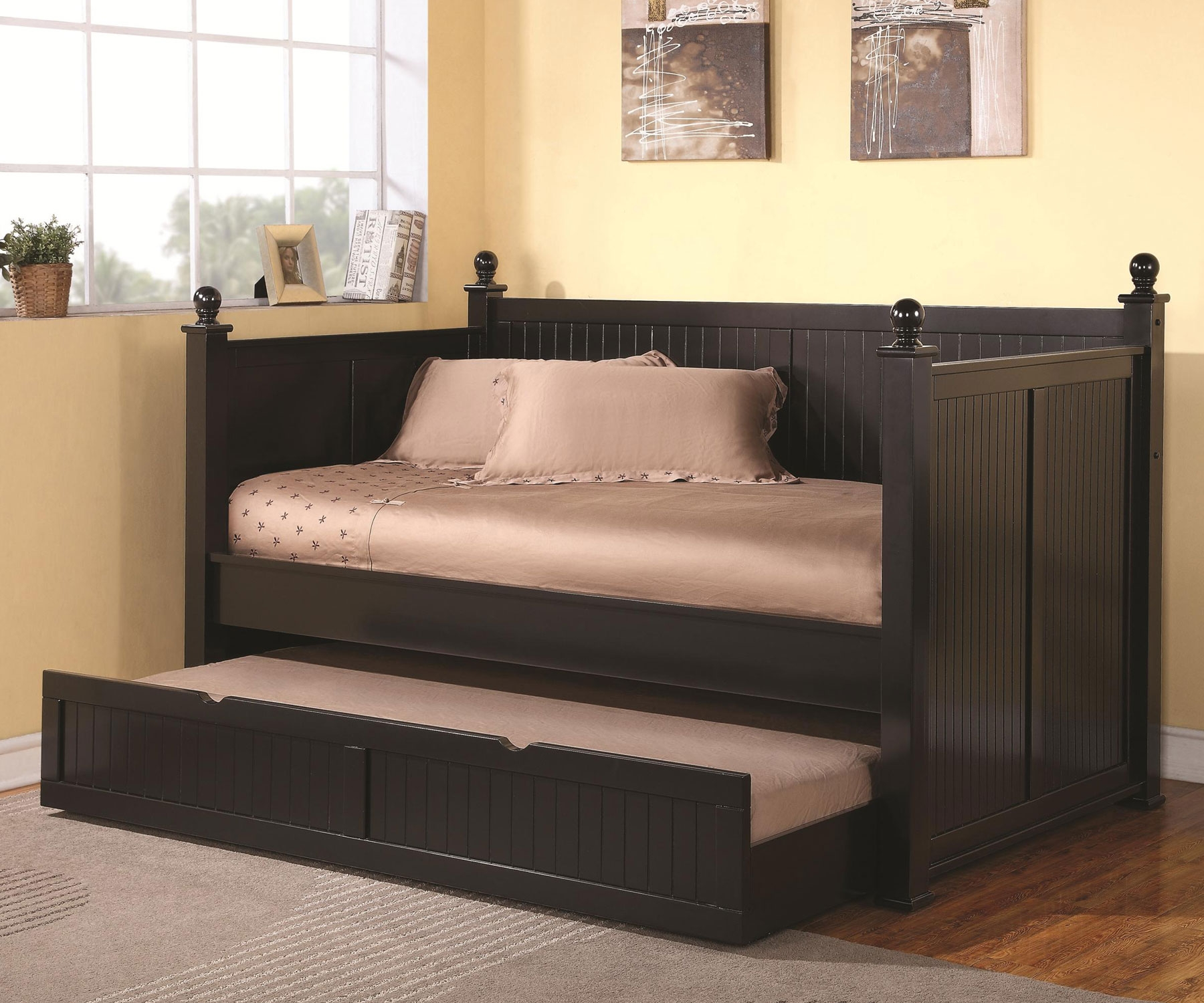 black wood daybed with additional trundle feature light grey rug floor wood floor system two abstract