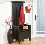 black wood finish corner bench with cloth hamger on top an artisic dark vase with beautiful flower an entrance mat solid wood floors a main entrance door with canvas panel