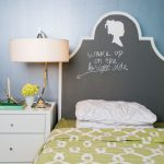 blackboard headboard with decorative woman picture and short message sidetable with cabinets a table lamp