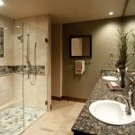 blue small mosaic tiles with transparent walk in shower and cool shower head with black floating vanity with double round sinks and greenery and recessed small ceiling lamps