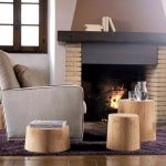 bricks wall construction for fireplace and dark wood top mantle fireplace a grey sofa with pillow three stump tables in different size and height dark brown ceramic tiles floors beautiful purple carpet