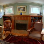 built in wood fireplace mantel with beautiful craftsman and  bookshelves a wood chair a cozy reading chair brown sofa with pillow a large and luxurious rug floors
