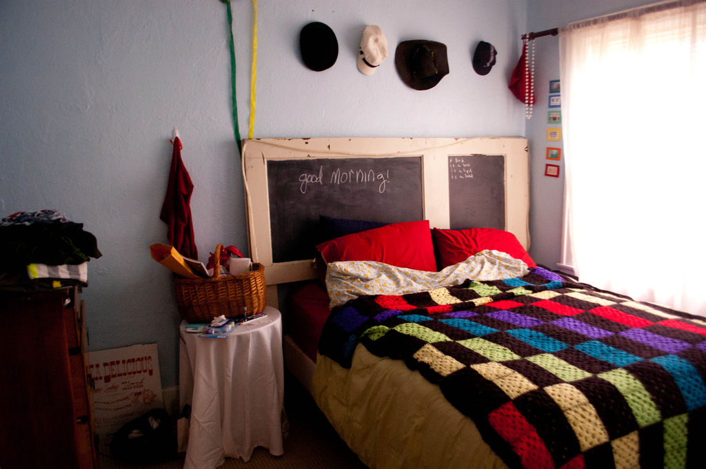 chalkboard headboard with cream wood frames colorful square-shaped bedcover and red pillows   round bedside table with white table cover