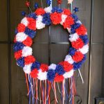 cheerful wreath of fourth of july design made of shipon cloth roses in blue white and red with stars decoration on top and horse tail in the lower design