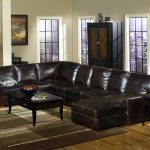 classic brown leather double chaise sectional design with rectangle wooden table upon brown ombre area rug and cabinet upon wooden floor with bar glass window