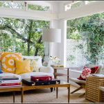 colorful sun porch design with open plan and glas wall and ceiling with rattan seating and wooden table and colorful yellow blue cushions and red pillow