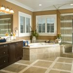 Cool Bathroom Remodeling With Wooden Bathroom Vanity Unit Plus Mirror And Fresh Vase Combined With Bath Tub And Shower With Glass Door Together With Tile Wall And Floor And Wall Lighting
