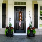 cool black door idea with christmad decoration with carved design flanked between two bunch of christmas flower before black pave patio