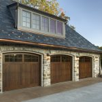 cool garage doors for three cars with wooden gararage door material and glass windows on tops plus wall scones and natural walls plus concrete floor