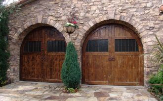 cool garage with solid wooden garage door with windows for double cars combined with awesome natural wall and beautiful garden and natural stone floor