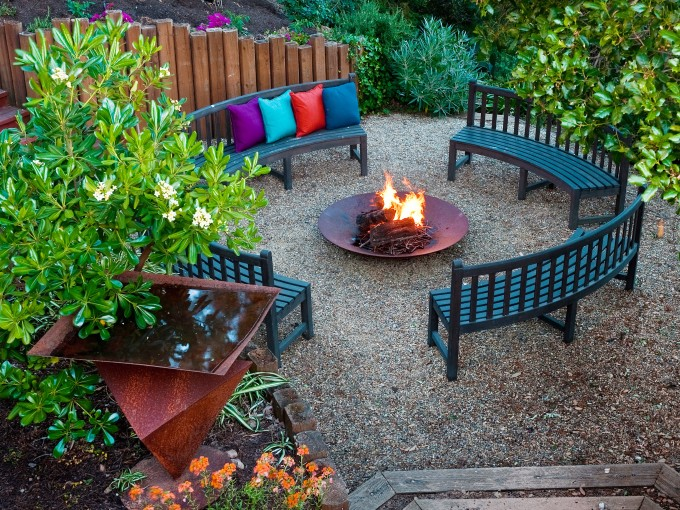 cool log fencing for patio some curved wood chairs with colorful pillows a fire pit table