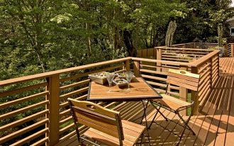 cool outdoor balcony design with wooden deck flooring and adorable wooden seating and table and horizontall railing deck with greenery