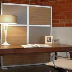 cool  room divider with woodboard and semi glass board panels a large wood table as workstation a table lamp a chair