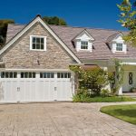 cool wooden carriage garage doors in white scheme plus windows on top combined with  natural stone wall  combined with brick paver pattern floor and garden