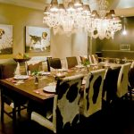 cowhide dining chairs for large and exclusive dining room a large wood dining table for 12 dining chairs a beautiful crystal pendant chandelier  hardwood floors two pets paintings
