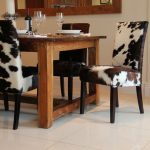 cowhide dining chairs heavy wood dining table some wine glasses a bottle of wine white ceramic floors