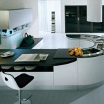 curved kitchen island with cool chair and wooden countertop plus table lamps and sink plus picture and wooden floor