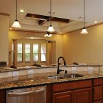curved kitchen island with granite countertops plus sink and pendant lights and oven plus lighting with fan